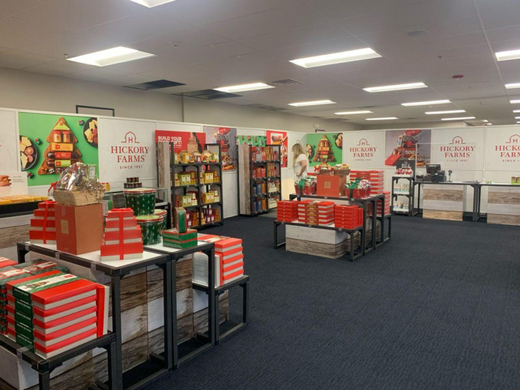 A large store with temporary hoarding walls and displays of boxed food and gift baskets